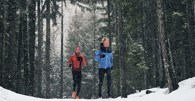Läufer und Läuferin laufen im Schnee