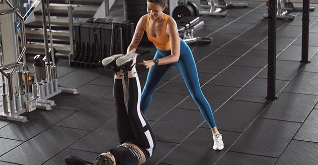Frau unterstützt liegende Frau bei Kraftübungen für den Bauch