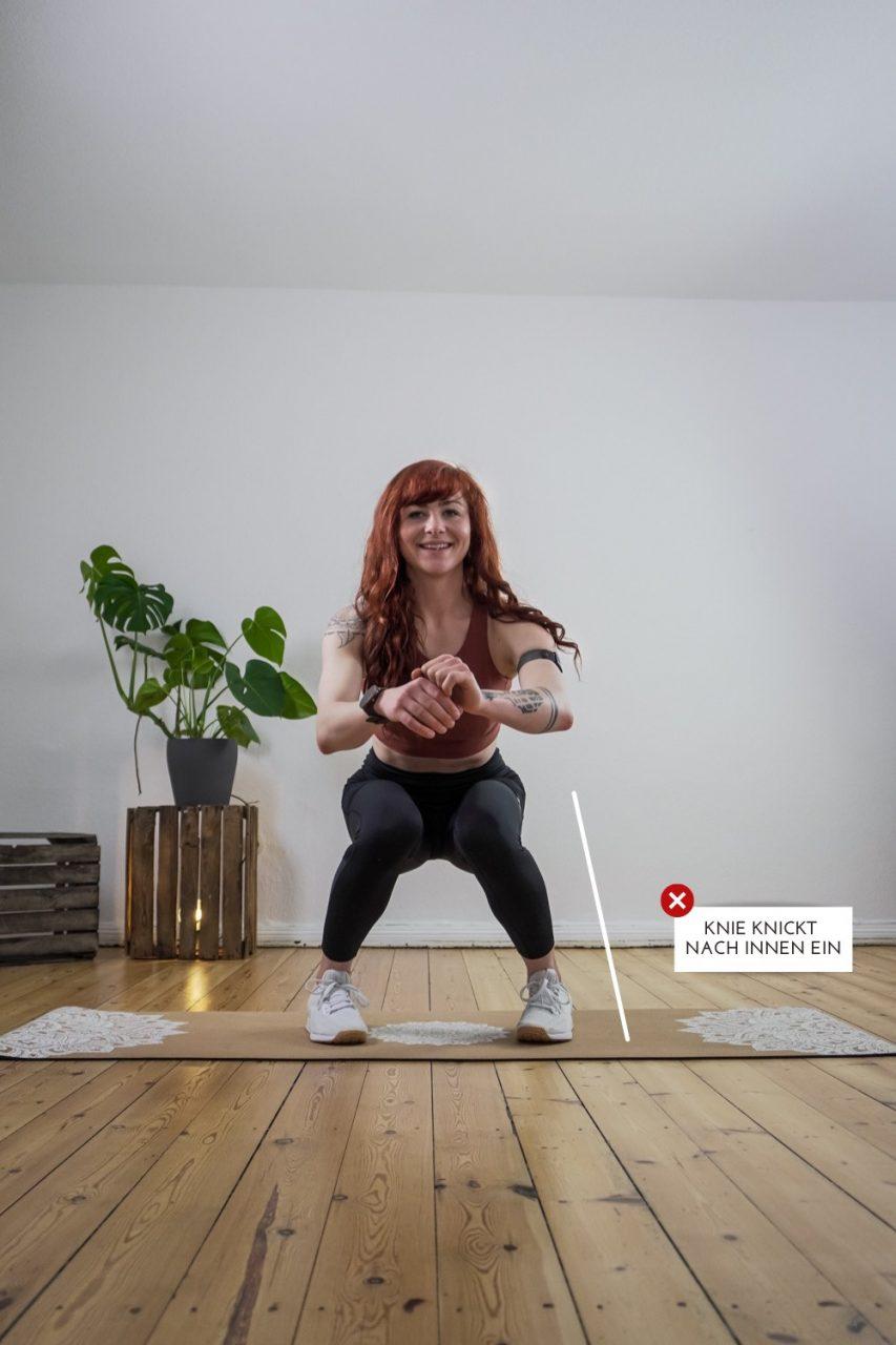 Frau zeigt mögliche Fehler bei Kniebeuge