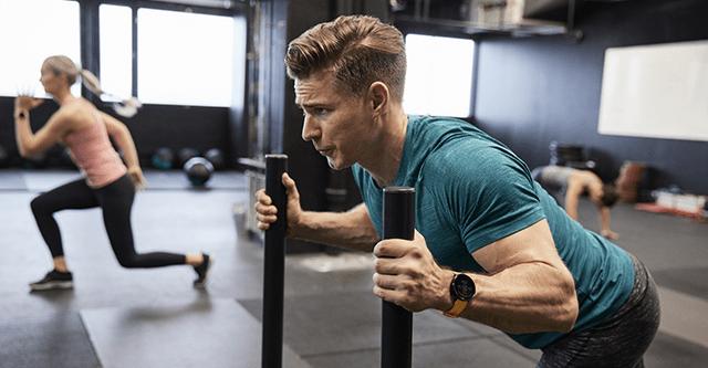 Mann schiebt Gewichtschlitten im Fitnessstudio