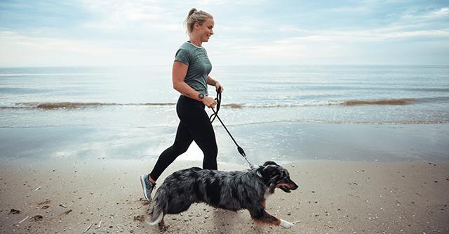 Fit ohne Sport - Frau geht mit Hund am Strand spazieren